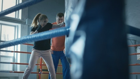 Woman training boxing with trainer on the ring