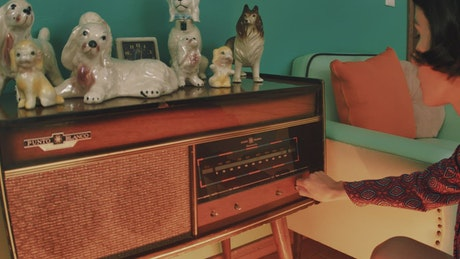 Woman turning on an old radio
