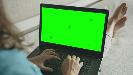 Woman types on greenscreen laptop on sofa
