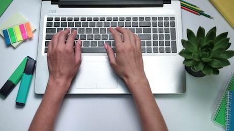 Woman typing on an English keyboard