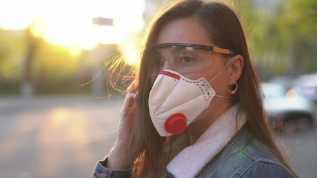 Woman using a face mask in the street