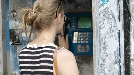Woman using a public telephone