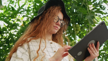Woman using a tablet at a greenhouse