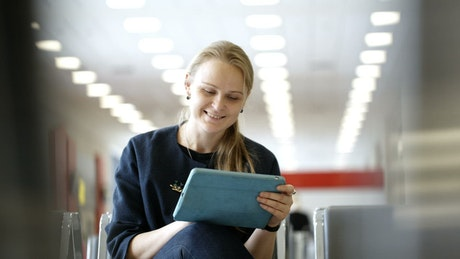 Woman using a tablet in a waiting room
