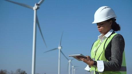 Woman using a tablet in a wind turbine field
