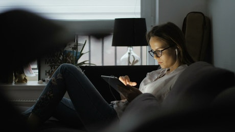 Woman using a tablet lying on the couch