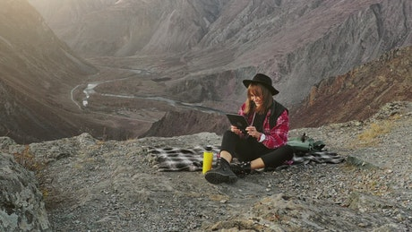 Woman using a tablet on top of a crag