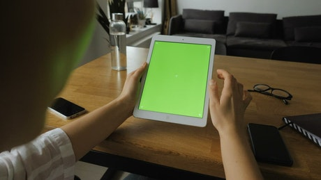 Woman using a tablet with a green screen