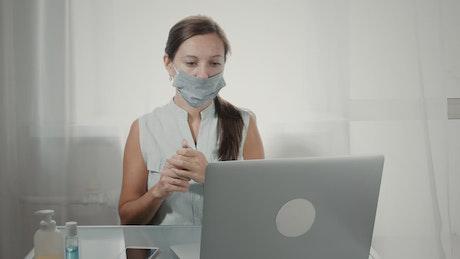 Woman using hand sanitizer before using laptop