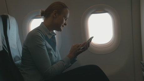 Woman using her phone during a flight