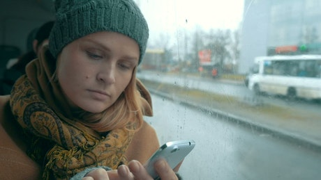 Woman using her phone on a rainy day