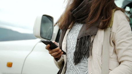 Woman using mobile GPS outside car