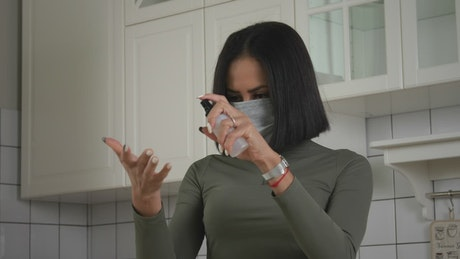 Woman using the hand sanitizer in the kitchen