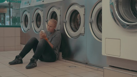 Woman waiting for her laundry to finish