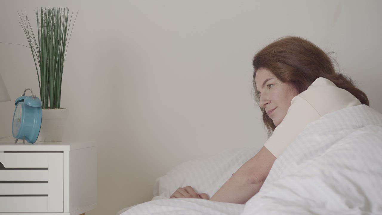 Woman waking up while turning off her alarm clock - Free