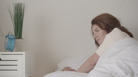 Woman waking up while turning off her alarm clock