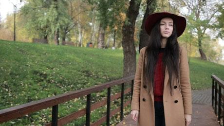 Woman walking alone through park in autumn