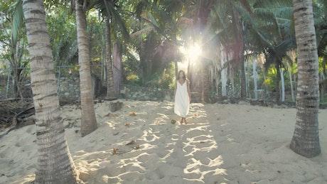 Woman walking among palm trees
