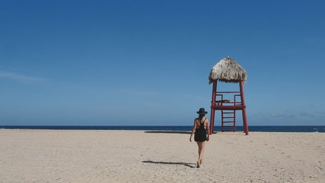 Woman walking barefoot on the beach