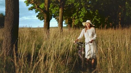 Woman walking bicycle through field enjoys afternoon sun