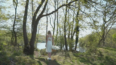 Woman walking by a lake with flowers