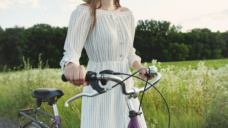 Woman walking by the countryside with her bicycle