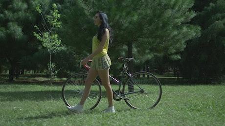 Woman walking her bike through park