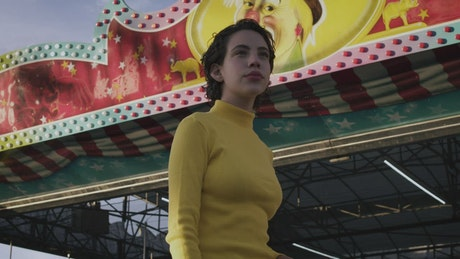 Woman walking in front of mechanical rides