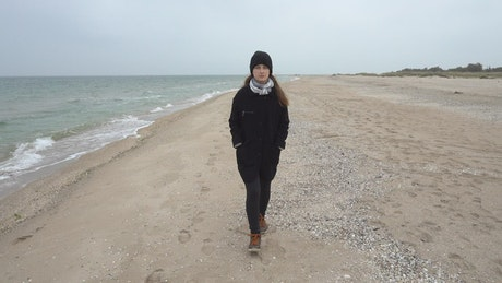 Woman walking on a cold beach
