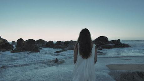 在朝着巨石的海滩上行走的女人