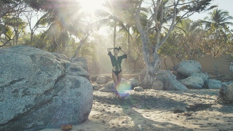 Woman walking slowly through rocks on a beach