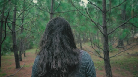 Woman walking through the branches in a forest