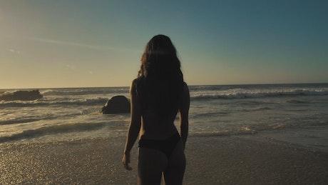 Woman walking towards the ocean