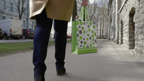 Woman walking with a green bag