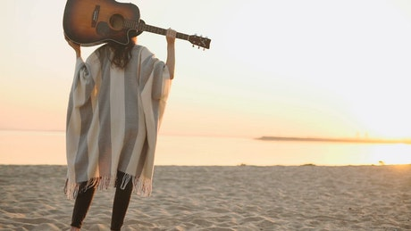 Woman walks on sunset beach with acoustic guitar