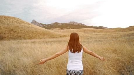Woman walks through a dry meadow feeling freedom