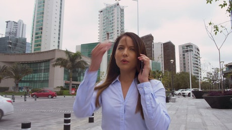 Woman walks through the city speaking on the phone