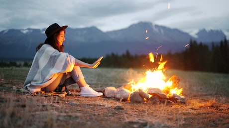 Woman warming her hands over a hot campfire