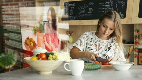 Woman watches futuristic tutorial while chopping vegetables