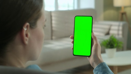 Woman watching to a green screen smartphone