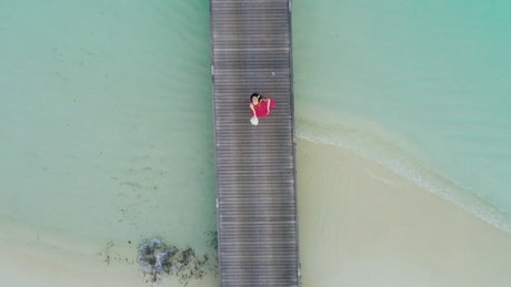 Woman waving from a pier at the beach