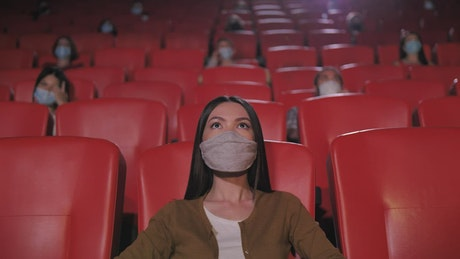 Woman wearing a mask at the cinema
