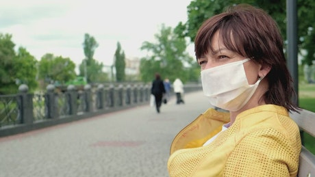 Woman wearing face mask on park bench
