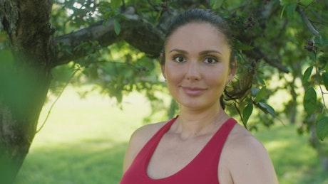 Woman wearing sportswear smiling in a park