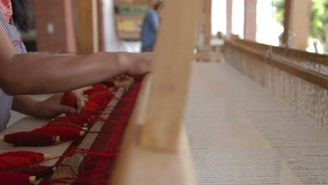 Woman weaving a cloth on a large wooden loom