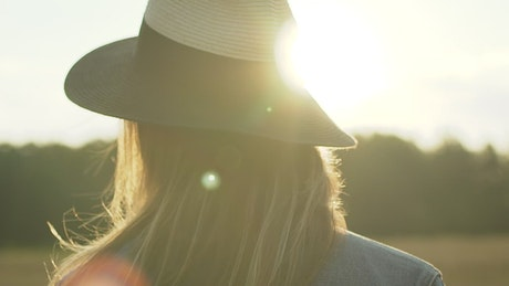 Woman with a hat looking at the sunset