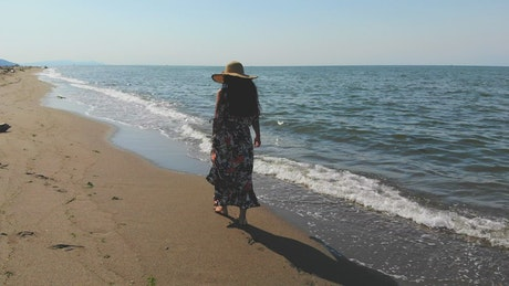 Woman with a hat walking on an empty beach