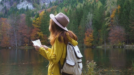 Woman with a map in in the forest landscape