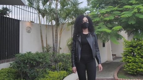 Woman with a mask walking through a neighborhood
