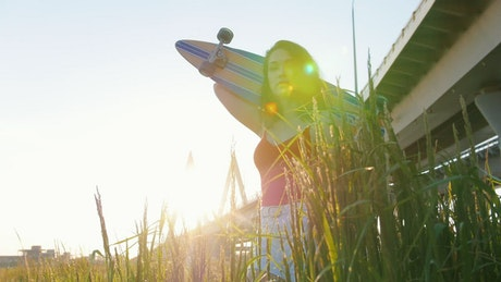 Woman with a skateboard under sunset light
